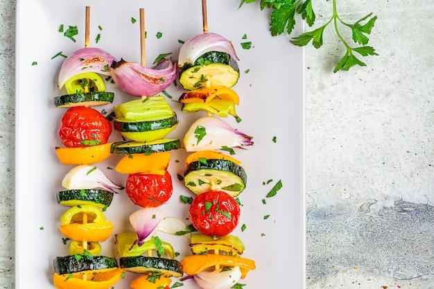 Spiedi di verdure arrostiti sul piatto rettangolare grigio, vista dall'alto, spazio di copia. concetto di cibo vegan.