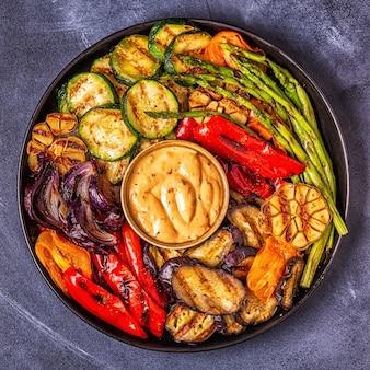 Verdure grigliate su un piatto con salsa, vista dall'alto.