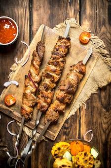 Verdure grigliate con un fragrante shish kebab di montone.su fondo di legno.