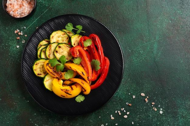 Verdure grigliate zucchine, peperoni rossi e gialli, peperoni e bouquet di coriandolo sulla griglia. vista dall'alto. concetto di barbecue.