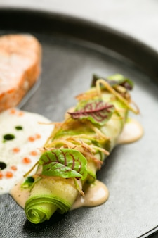 Rotolo di zucchine grigliate con chiusura microverde su piatto in ceramica nera e tavolo in cemento