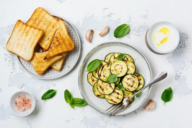 Insalata di zucchine grigliate con foglie di basilico, salsa allo yogurt e pane fritto in un semplice piatto di ceramica su una superficie di cemento bianco