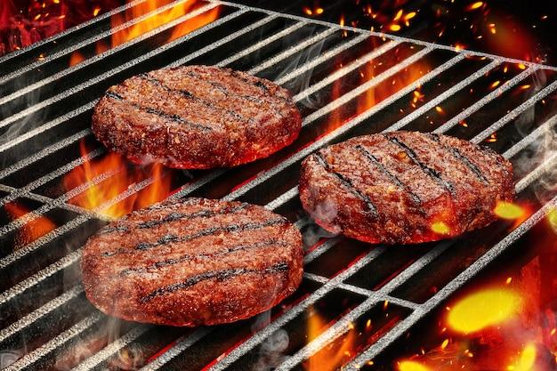 Processo di cottura alla griglia di preparazione di cotolette di maiale per hamburger di carne arrostita su griglia barbecue in metallo con...