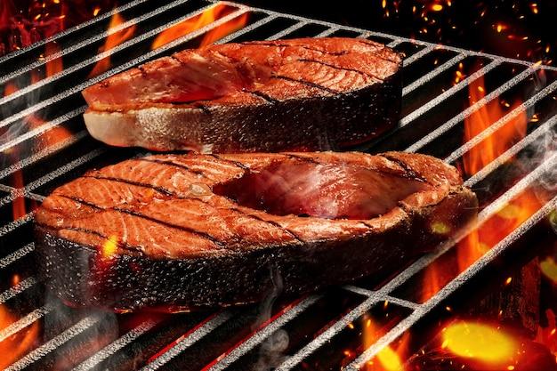 Processo di cottura alla griglia per preparare gustose bistecche di salmone. carne arrostita su barbecue estivo portatile in metallo griglia per barbecue con fuoco fiammeggiante brillante, fumo e carbone di legna. frutti di mare. concetto di cucina. avvicinamento