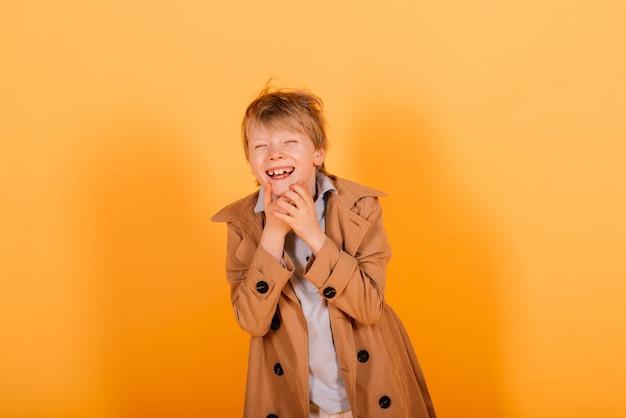 Smorfie emotivo redhead fasion boy in posa in uno studio giallo