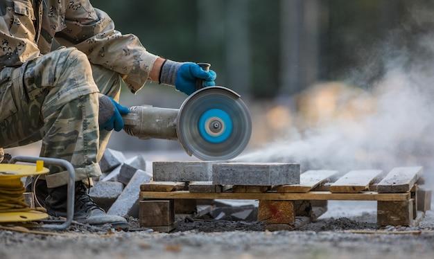 Il lavoratore della smerigliatrice taglia una pietra l'utensile elettricolavori di costruzione di strade