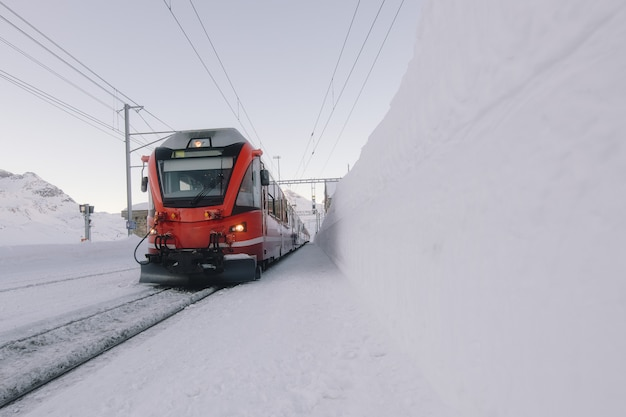 Grigioni treno rosso nel mezzo di molta neve