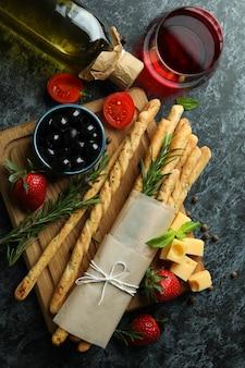 Grissini, snack e vino su sfondo nero smokey
