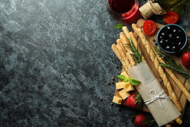 Grissini, snack e vino sulla superficie nera affumicata