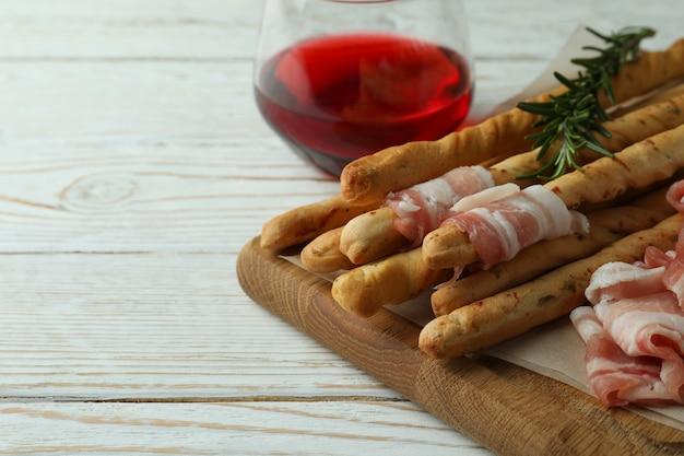 Grissini con pancetta e vino su fondo di legno bianco