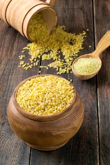 Semole di bulgur di grano duro e couscous in pentole di legno cucchiai su un tavolo di legno
