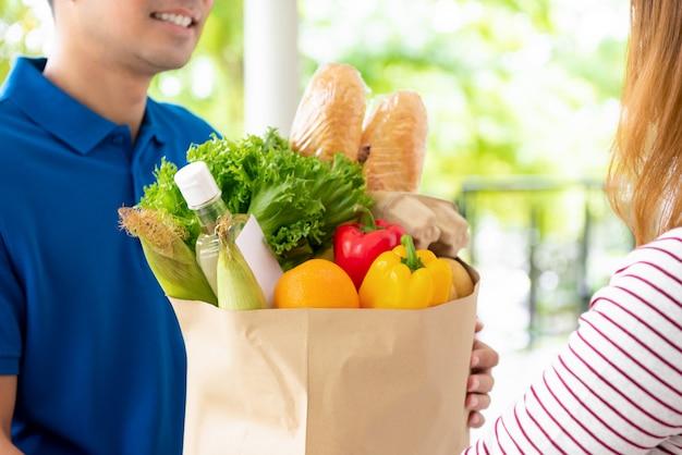 Generi alimentari consegnati al cliente a casa da un fattorino, per il concetto di servizio di ristorazione online