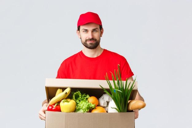 Consegna di generi alimentari e pacchi, covid-19, quarantena e concetto di shopping. corriere bello con berretto e maglietta dell'uniforme rossa, porta un pacco di generi alimentari, consegna della scatola a casa del cliente, spedizione veloce