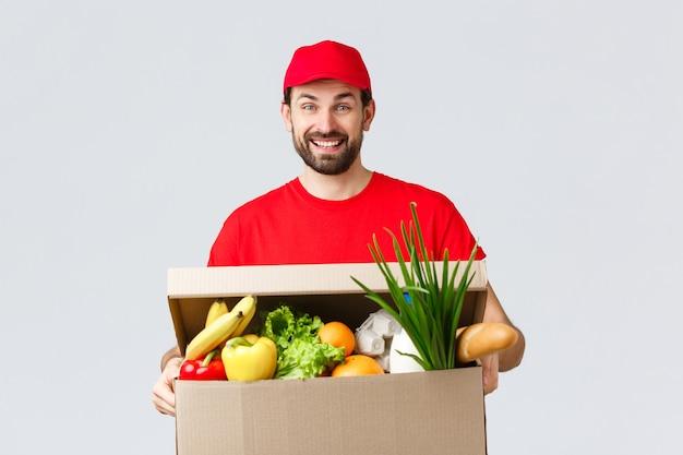 Consegna di generi alimentari e pacchi, covid-19, quarantena e concetto di shopping. sorridente fattorino in uniforme rossa, porta l'ordine del cliente, tiene in mano un pacco di scatole di cibo, si diverte ad aiutare le persone a trasferire le merci