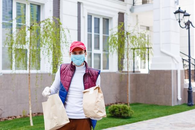 Fattorino della spesa che indossa guanti medici e maschera facciale. shopping online e consegna di generi alimentari, vino e cibo. autoquarantena durante la pandemia di coronavirus. corriere del servizio di consegna cibo