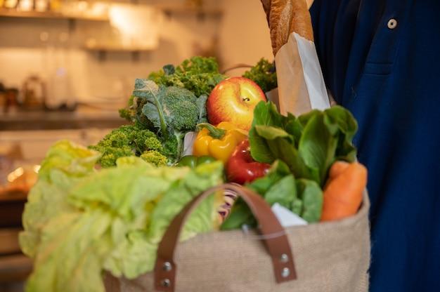 Prodotti alimentari in sacchetto di carta, frutta e verdura, vagano, vegetariano, ecologico, cibo sano su tavola di legno, salva la terra, concetto di stile di vita.
