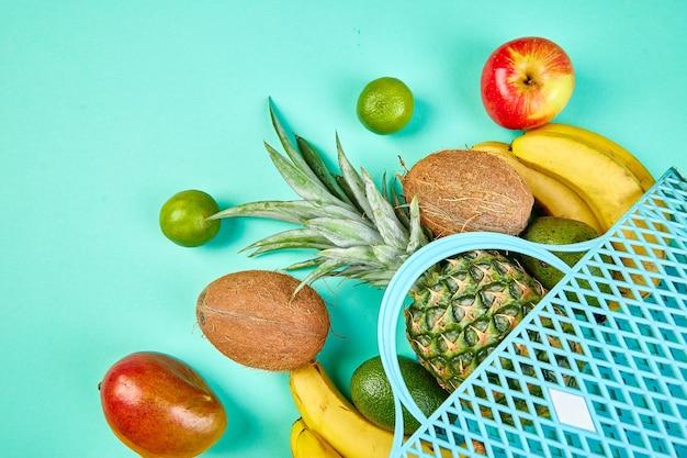 Borsa della spesa con frutta esotica biologica su sfondo blu.