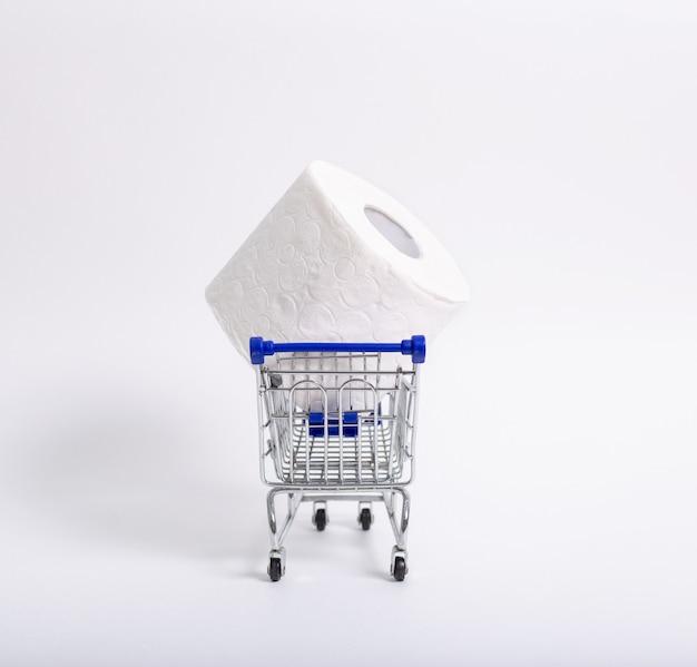 Carrello della spesa con rotoli di carta igienica dietro. concetto di mancanza di carta igienica nei negozi a causa del coronavirus, covid-19