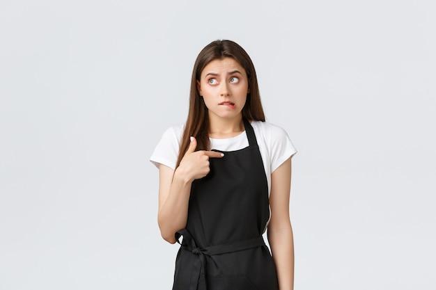Dipendenti del negozio di alimentari, piccole imprese e concetto di caffetterie. ansioso e carino barista che morde il labbro in modo imbarazzante, guardando in alto meditando e indicandosi dubbioso, indossando l'uniforme nera del grembiule