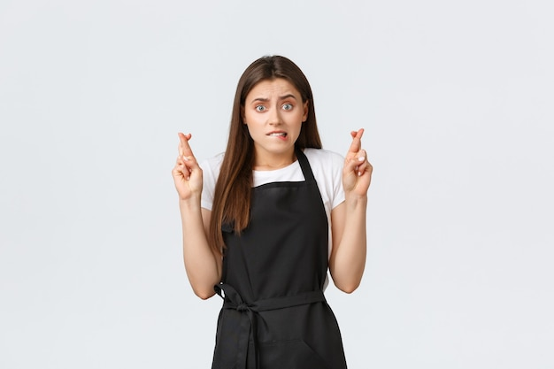 Dipendenti del negozio di alimentari, piccole imprese e concetto di caffetterie. ansioso barista femminile carino in grembiule nero che morde il labbro preoccupato e incrocia le dita, pregando o esprimendo desideri.