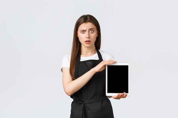 Dipendenti del negozio di alimentari, piccole imprese e concetto di caffetterie. barista ragazza carina confusa e perplessa in grembiule nero alza un sopracciglio scioccato e mostra lo schermo del tablet digitale