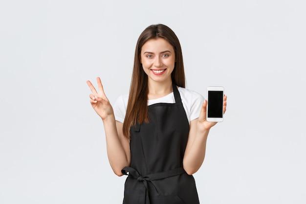 Dipendenti del negozio di alimentari, piccole imprese e concetto di caffetterie. il simpatico barista sorridente in grembiule nero pubblicizza un'app online, lo shopping in internet, mostra lo schermo del telefono cellulare e il segno della pace