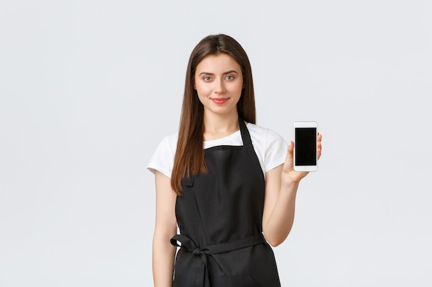 Dipendenti del negozio di alimentari, piccole imprese e concetto di caffetterie. la commessa sorridente e carina consiglia di scaricare l'app per lo shopping online, che mostra il display dello smartphone, l'applicazione pubblicitaria.