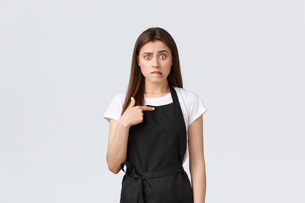 Dipendenti del negozio di alimentari, piccole imprese e concetto di caffetterie. barista femminile imbarazzata e preoccupata in grembiule nero che si morde il labbro e sembra ansiosa, indicandosi. copia spazio