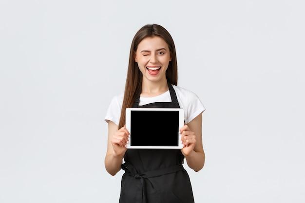 Dipendenti del negozio di alimentari, piccole imprese e concetto di caffetterie. barista femminile sorridente felice emozionante, lavoratore del caffè in grembiule che mostra il display del tablet digitale, pubblicità nuovo menu o ordine online.