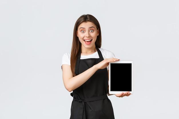 Dipendenti del negozio di alimentari, piccole imprese e concetto di caffetterie. commessa eccitata che mostra una bella pubblicità, sorride stupita mentre mostra il display della tavoletta digitale, sfondo bianco in piedi.
