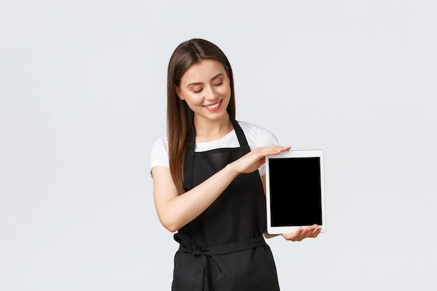 Dipendenti del negozio di alimentari, piccole imprese e concetto di caffetterie. amichevole commessa carina in grembiule nero che mostra lo schermo del tablet digitale e sorride al display del gadget, mostrando pubblicità.