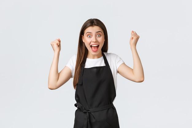 Dipendenti della drogheria, piccola impresa e concetto delle caffetterie. felice barista femmina in grembiule nero alzando le mani in su gioire, celebrando grandi successi o successi