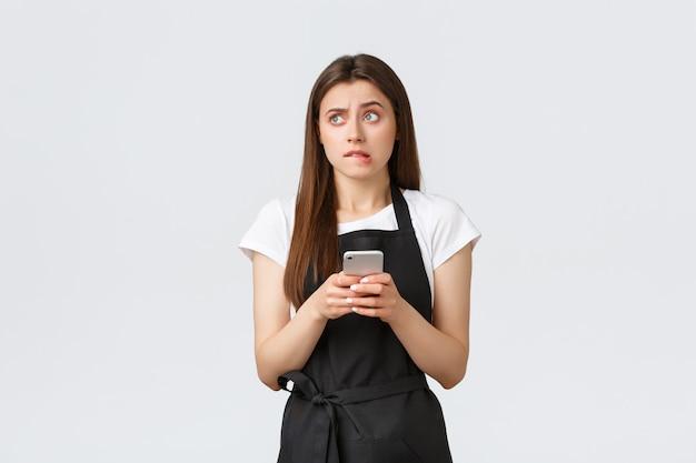 Dipendenti del negozio di alimentari, piccole imprese e concetto di caffetterie. indeciso perplesso barista ragazza carina in grembiule nero, guardando a sinistra insicuro, mordendosi il labbro e utilizzando il telefono cellulare, non sono sicuro di quale risposta.