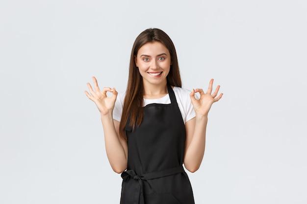 Dipendenti del negozio di alimentari, piccole imprese e concetto di caffetterie. barista femminile felice soddisfatta in grembiule nero che mostra il segno giusto e che morde il labbro allettante. la commessa soddisfatta consiglia di acquistare online