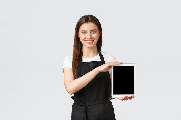 Dipendenti del negozio di alimentari, piccole imprese e concetto di caffetterie. sorridente commessa del negozio carino in grembiule nero che mostra lo schermo del tablet digitale. il lavoratore del bar suggerisce di ordinare online