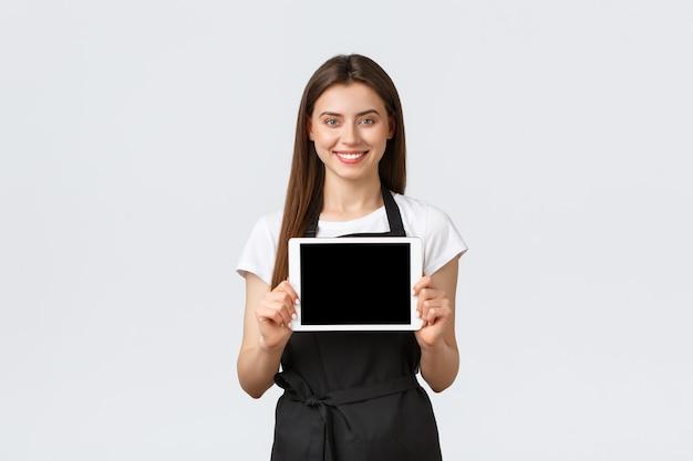 Dipendenti del negozio di alimentari, piccole imprese e concetto di caffetterie. sorridente commessa utile che mostra l'app per ordini online sullo schermo del tablet digitale, incoraggia a rimanere a casa il distanziamento sociale.