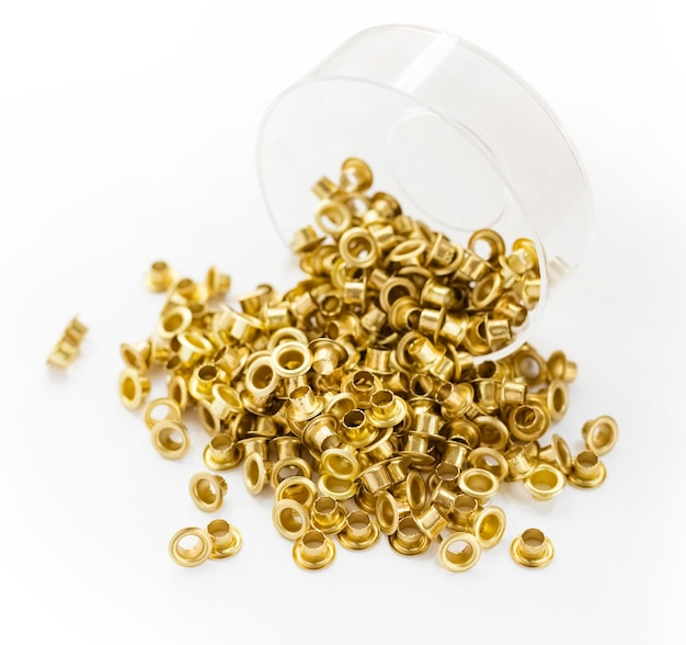 Occhielli incastonati su sfondo bianco occhielli in metallo, acciaio, ottone, rame dorato