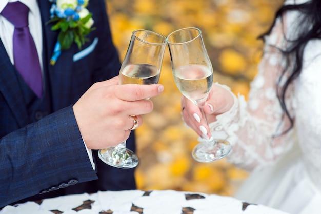 Lo sposo e la sposa stanno tenendo gli occhiali in primo piano le loro mani