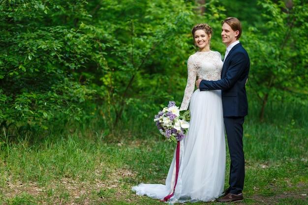 Sposo e sposa che tengono il bouquet da sposa con fiori lilla sullo sfondo della vegetazione
