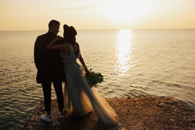 Sposo e sposa guardano il bellissimo tramonto arancione vicino al mare