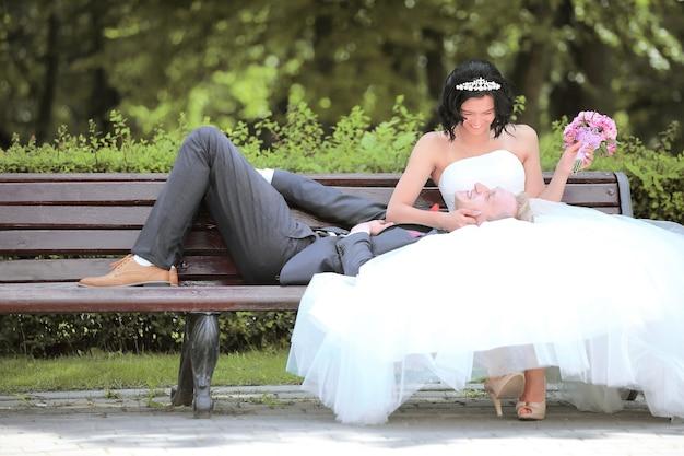 Sposo e sposa che si distendono su una panchina del parco