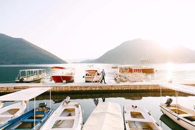 Lo sposo e la sposa camminano lungo il molo sulla costa della baia oltre gli yacht parcheggiati. foto di alta qualità
