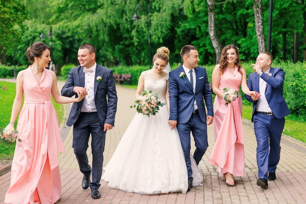Lo sposo e la sposa camminano con groomsman e damigella d'onore nel parco.