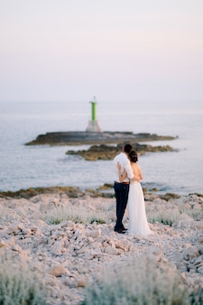 Lo sposo e la sposa in abito bianco sono in piedi, abbracciati, sul promontorio di punta planca, ammirando il faro verde nel mare in una giornata di sole. foto di alta qualità