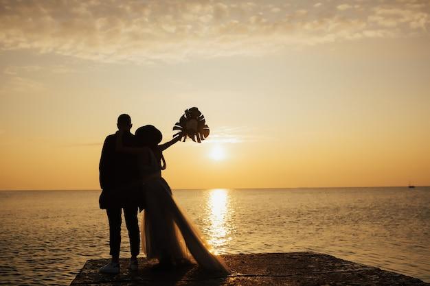 Sposo e sposa con bouquet in posa vicino al mare sul bellissimo tramonto
