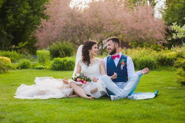 Lo sposo e la sposa nel loto di yoga posano in giardino