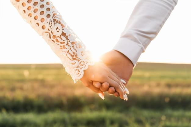 Mani degli sposi e con gli anelli, vista del primo piano del primo piano