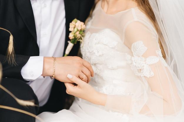 Mani dello sposo e spose con anelli