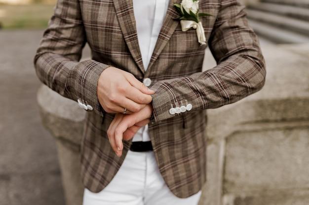 Lo sposo in giacca scozzese marrone guarda il suo anello al dito.