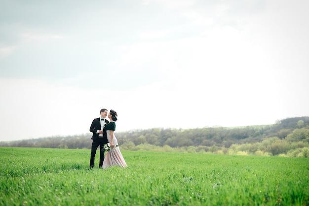 Lo sposo in abito marrone e la sposa in abito color avorio su un campo verde che si allontana in lontananza contro il cielo